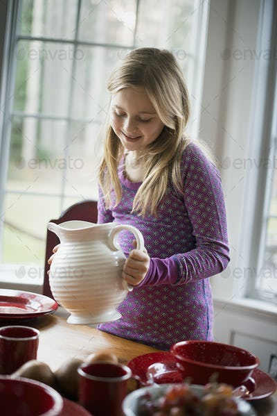 Children in a family home.  A girl  holding a white pottery jug. Table laid with crockery.