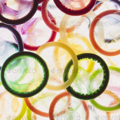 A large group of multi-colored condoms displayed on a white background. Heaped up.