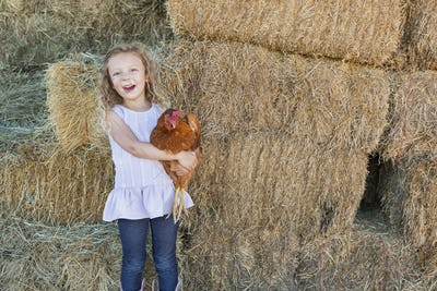 A young girl standing in a hay barn holding a chicken in her arms.