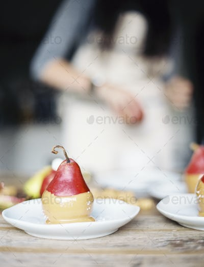 A woman in a domestic kitchen preparing organic pears in sauce for a dessert