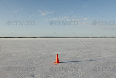 A solitary traffic cone on the Bonneville Salt Flats in the early morning light.
