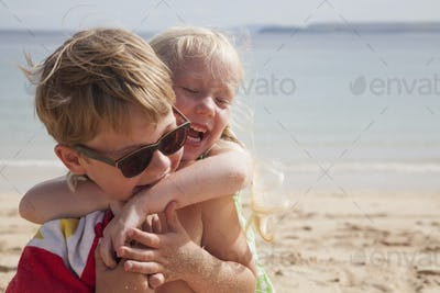 A brother and sister playfighting on the beach