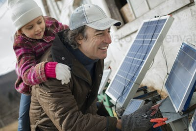 A man giving a child a piggybank while trying to connect the leads for solar power panels.