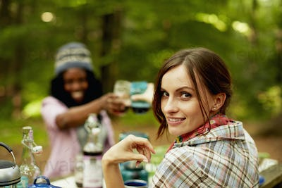 Two young woman drinking a toast at a picnic site or campsite in the woods.