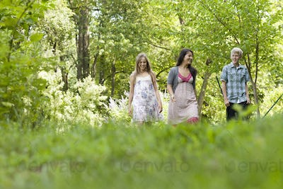 Three people, woman and children walking through woodland.