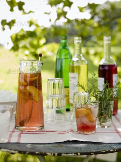 A buffet table set up in a garden for al al fresco meal. Drinks,bottles,a jug of punch and glasses.