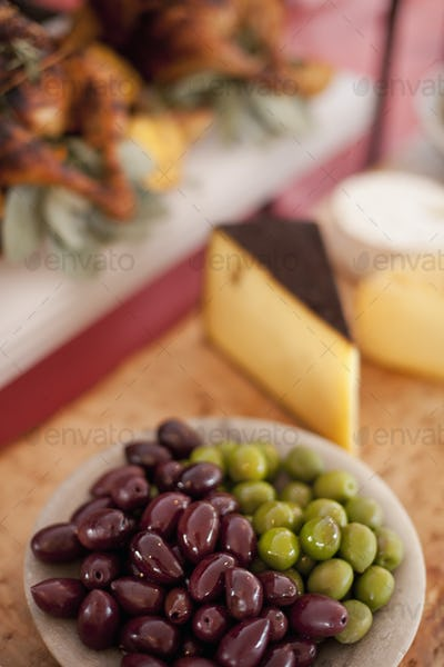 A buffet table,Organic food,A cheese board selection,and a plate of green and black olives.