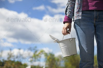 A woman carrying a white tin bucket with gardening tools, on an organic farm.