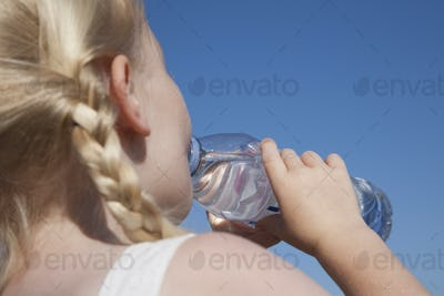 A young child with blonde hair in pigtails, drinking water from a clear bottle.