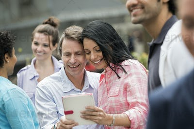 A group of men and women,a couple looking at a digital tablet screen.