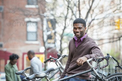 Outdoors in the city in spring. An urban lifestyle. A young man smiling at the camera. Bicycle rack.