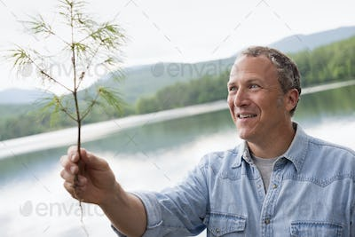 A man on the shore of a lake in New York state.