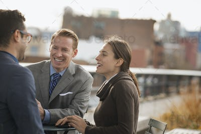 Three people standing in an open space between city buildings,talking to each other