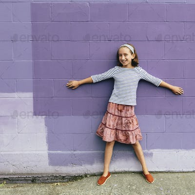 A ten year old girl in a tiered skirt, standing with her arms outstretched, leaning against a wall.