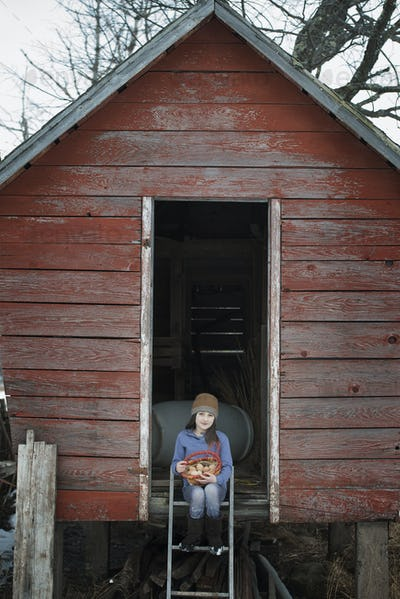 A girl sitting on the ladder of a henhouse with a basket of eggs.