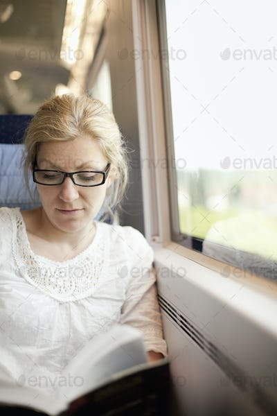 A woman sitting by a train window, reading a book.