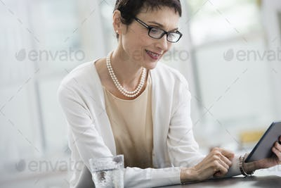 Young professionals at work. A woman in an office, using a digital tablet.