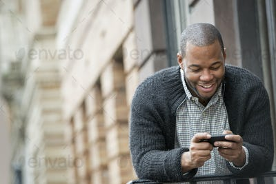 Outdoors in the city in spring. An urban lifestyle. A young man checking his phone and texting.
