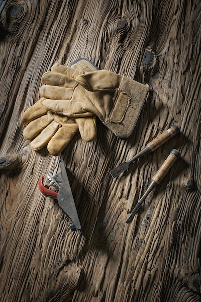 A reclaimed lumber yard workshop. A pair of leather working gloves, and handheld traditional tools.