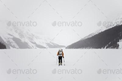 A skier ,a frozen lake on the Wapta Traverse,a mountain hut-to-hut ski tour in Alberta,Canada.