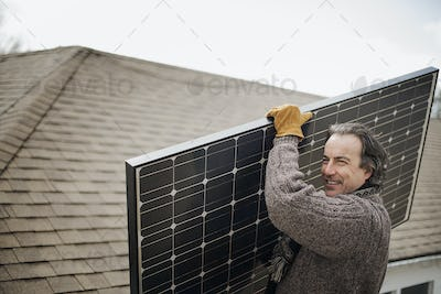 A man carrying a large solar panel across a farmyard.