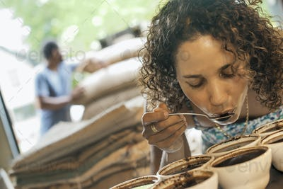 A woman sampling the coffee roast taste in a coffee processing shed