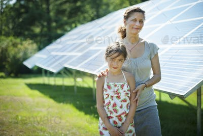 A child and her mother in the fresh open air,beside solar panels on a sunny day at a farm