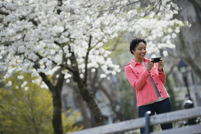 Woman holding her mobile phone and smiling outdoor in spring in the city