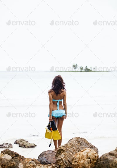 A young woman holding snorkeling gear on the Samana Peninsula in the Dominican Republic.