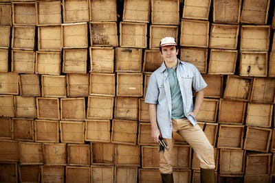 A farmer standing in front of a wall of stacked wooden crates for produce.