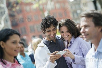 Group of men and women,a couple at the centre looking at a cell phone outdoors in a city park