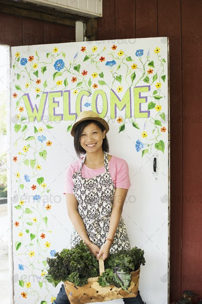 A young Asian woman by the Welcome sign at a farmstand with a large basket of vegetables