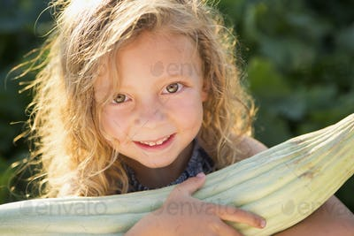 A young girl with long red curly hair outdoors in a garden holding a large fresh corn on the cob.