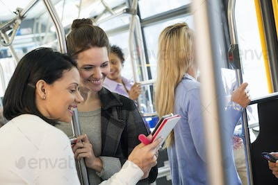 People,men and women on a city bus, Two women looking at a handheld digital tablet.