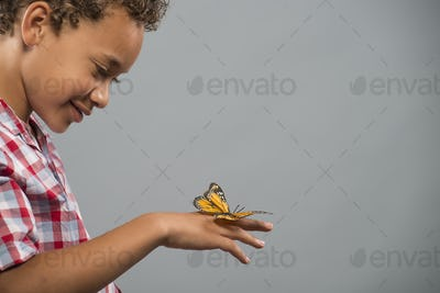 A child with a butterfly on his hand, keeping very still.