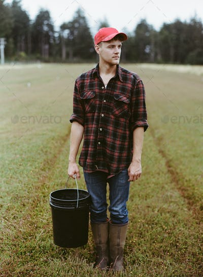 A young man working on the land,harvesting a cranberry crop.