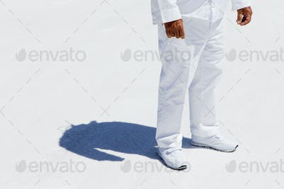 A man in white overalls,a race official timekeeper at a car racing event on salt flats