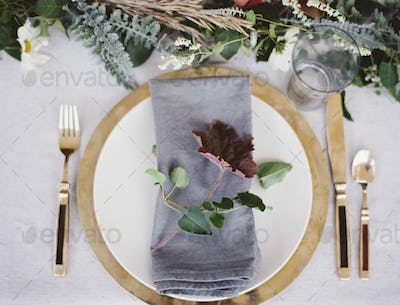 A table top and place setting with cutlery and plate. A napkin and foliage table decoration.