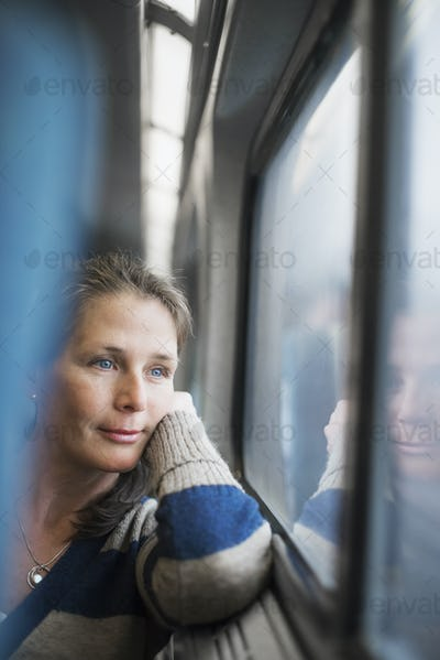 A woman sitting at a window seat in a train carriage resting her head on her hand