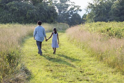 A man and a young girl walking down a mown path in the long grass holding hands.