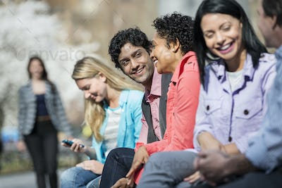 Five people in a park in spring,one looking at a mobile phone.