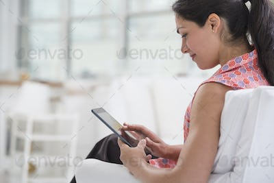 Professionals in the office. A light and airy place of work. A woman seated using a digital tablet.