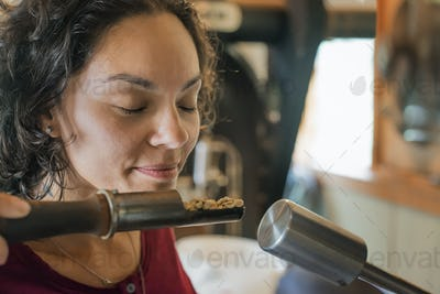 A person testing and smelling the aroma of the coffee at a bean processing shed