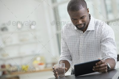 A businessman sitting holding a glass of water using a digital tablet.
