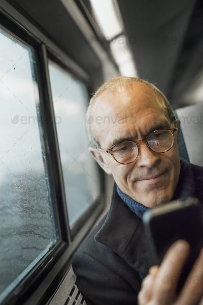 A mature man sitting by a window in a train carriage,using his ,mobile,keeping in touch on the move.