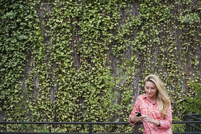 Young blonde haired woman checking her smart phone in a city park by a living wall.