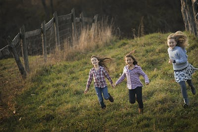 Three children running down a hill on an organic farm.