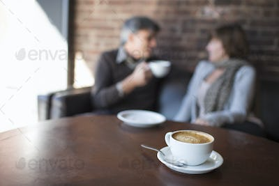 Two people sitting in a coffee shop having coffee
