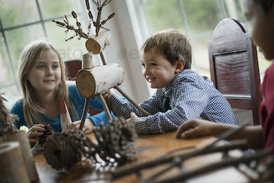 Three children sitting at a table in family home. A twig reindeer in the centre