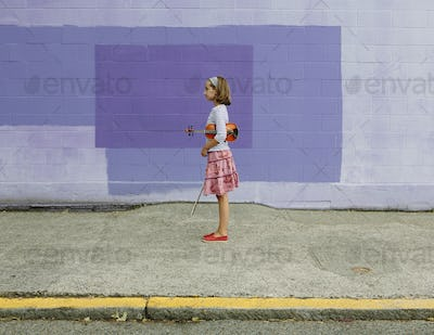 A ten year old girl holding a violin under her arm and a bow, purple background